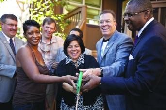 Commissioner Fish with Proud Ground representatives and Minority Homeowners Association cutting ribbon on a new house