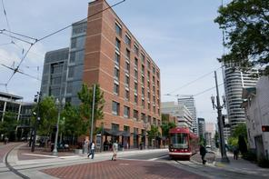 PSU Urban Center building pictured with pedestrians and a train